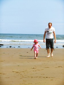 Father playing with his daughter on the beach near Whitby