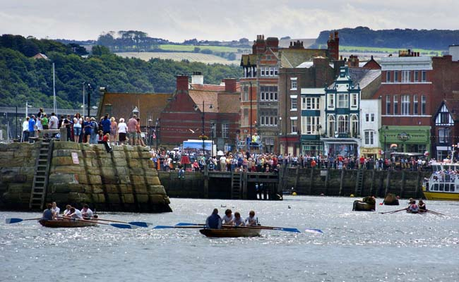 One of the rowing races at the Regatta – crowds line the harbour as the boats race to the finish – © Ceri Oakes/Whitby Gazette