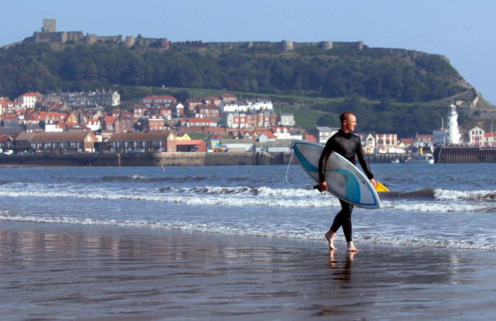 Surfer on the beach at Scarborough looking out to sea