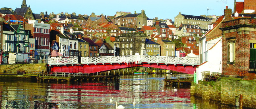 Whitby swing bridge with the town crest displaying the snakes of St Hilda of Whitby