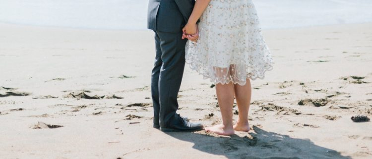 bride and groom holding hands and standing on the beach at their Whitby wedding venue