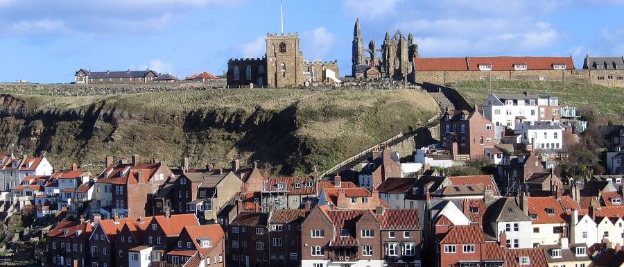 Byen Whitby i dag med klosterruinene kneisende over