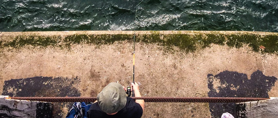 man fishing off Whitby's west pier