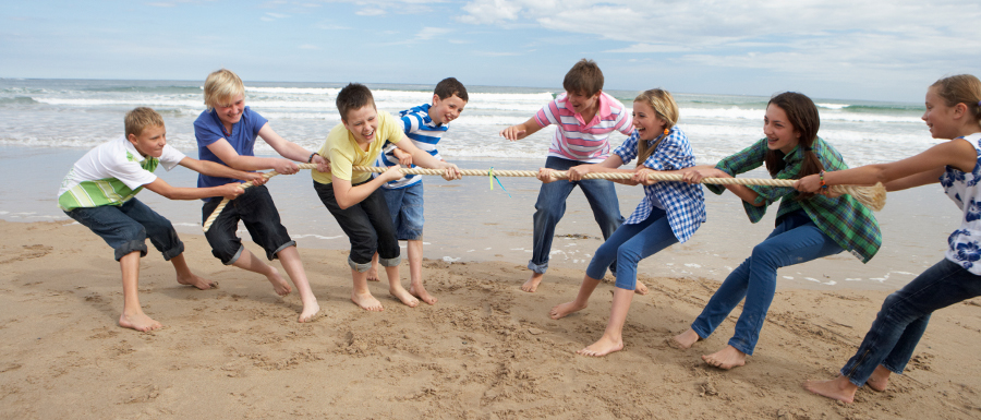 children playing tug of war on the beach