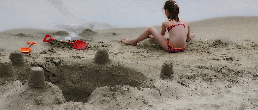 girl on the beach next to a big hole and sandcastles