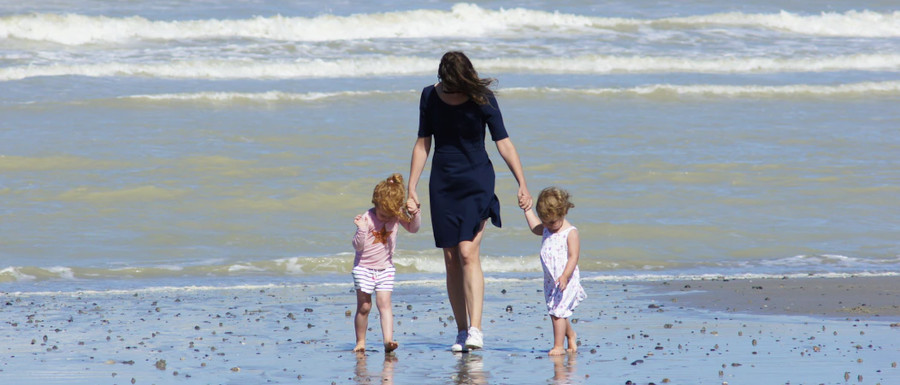 mum and two children walking on the beach