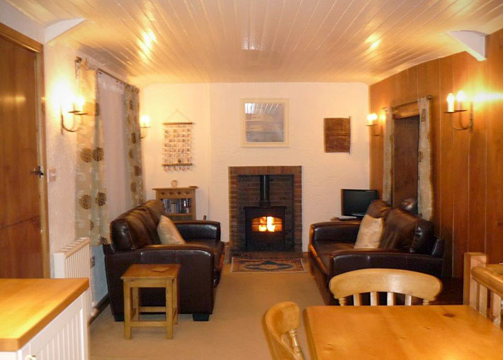 Open plan living area with leather sofas and wood burning stove